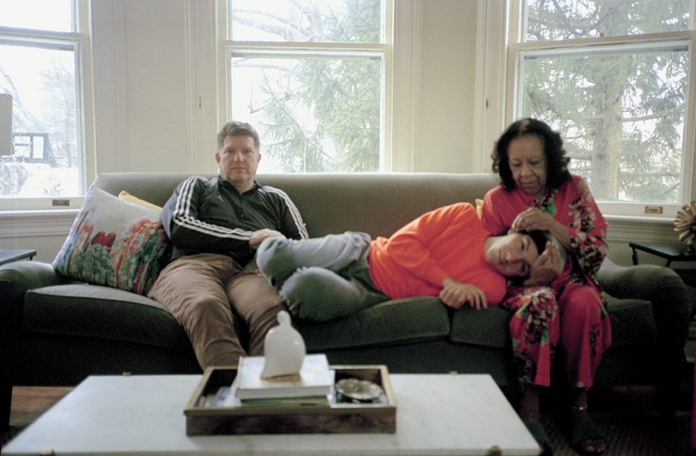 Family members sat on a sofa, with one member laid across the others