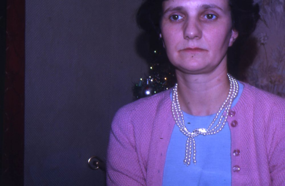 Lady in a pink cardigan sat at the dinner table