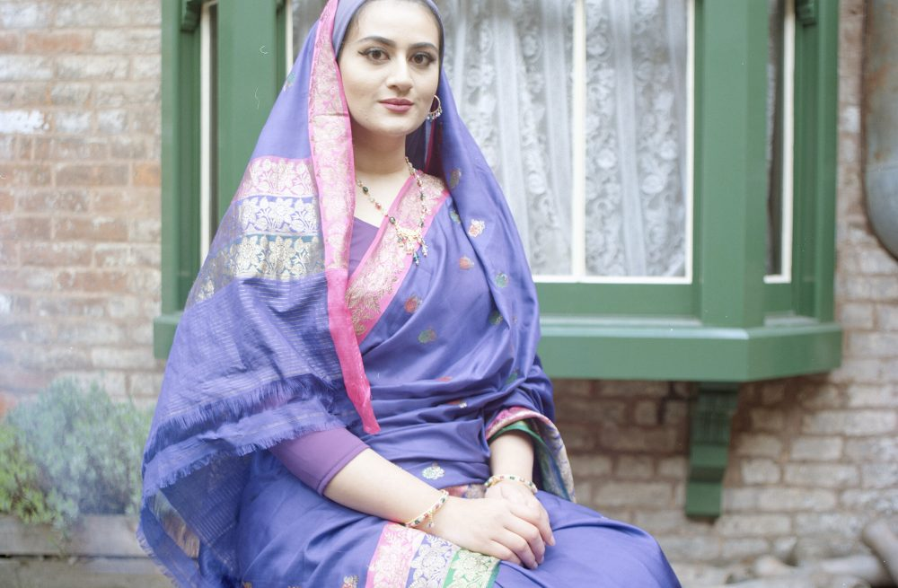 Woman in traditional Pakistani dress by a window