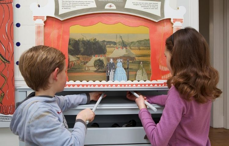 Children playing with the play theatre at Down House