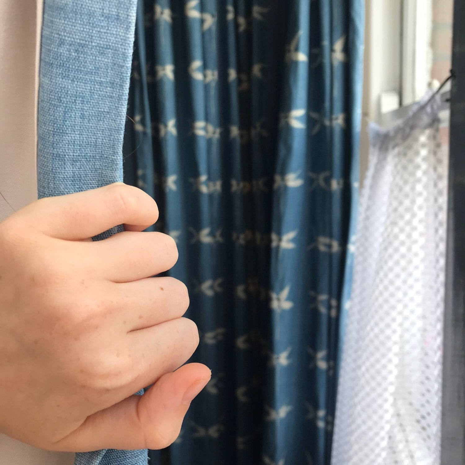 Person pulling back a curtain in hide and seek