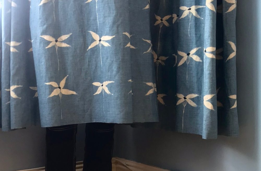 Person hiding behind a curtain