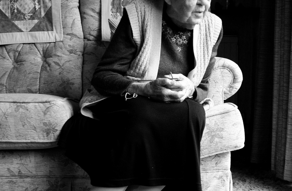 Grandma sitting on her sofa looking out