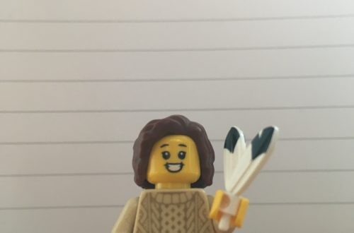Lego figure holding a quill in front of lined paper