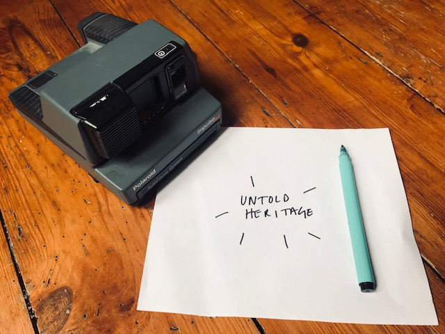 Polaroid camera sitting on top of a note