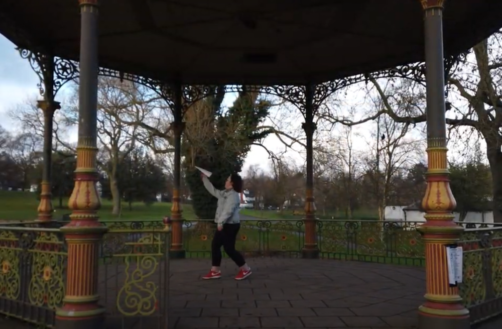 Girl throwing a paper air plane on a bandstand