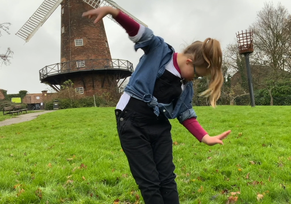 Girl dancing in front of a windmill